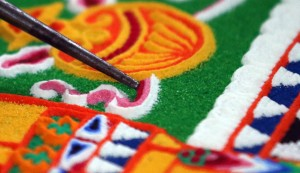SALISBURY, ENGLAND - OCTOBER 03: A Tibetan Monk from the Tashi Lhunpo Monastery, helps complete a Chenrezig Sand Mandala in Salisbury Cathedral's Chapter House on October 3, 2013 in Salisbury, England. The monks, who started the painstaking process of creating the sand mandela with millions of grains of coloured sand on Monday, will end it tomorrow in a destruction ceremony and procession to the River Avon. The monks who currently live in exile in India are visiting various places in the UK and Europe and will complete two more sand mandelas - which are an artistic tradition of Tibetan Buddhism and are a symbolic picture of the universe representing an imaginary palace - before returning home to their monastery in late November. (Photo by Matt Cardy/Getty Images)